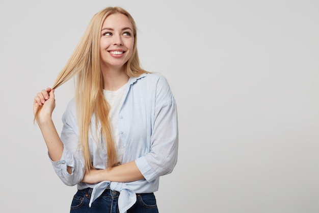 Schöne blonde dame, die freizeitkleidung trägt, mit breitem lächeln beiseite schaut und ihre haare zieht, isoliert