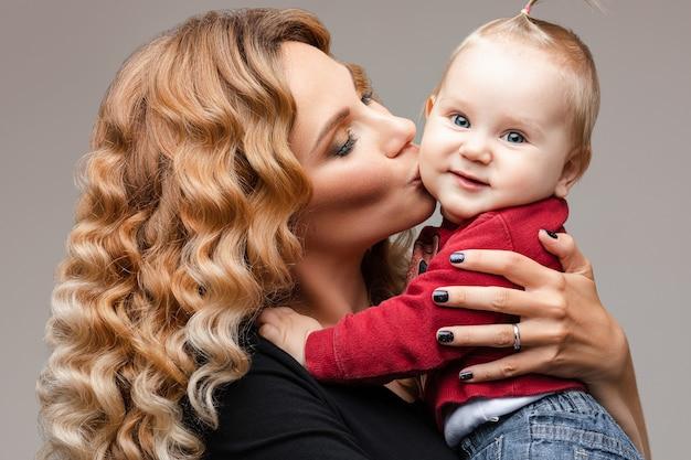 Schöne blonde dame, die ihr lächelndes kind hält und sanft seine wange küsst
