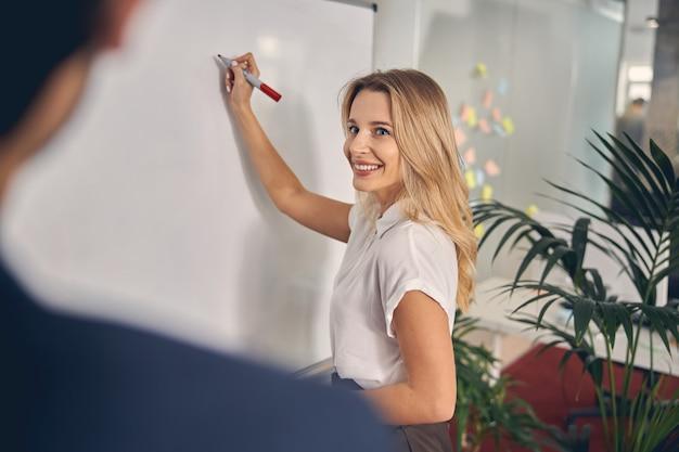 Schöne blonde dame, die kollegin anschaut und lächelt, während sie sich im büro notizen an bord macht