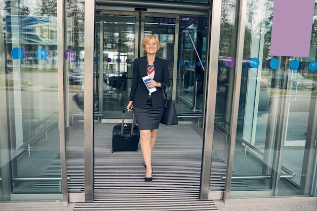 Schöne blonde dame im eleganten rockanzug mit reisekoffer und lächelnd beim verlassen des flughafenterminals