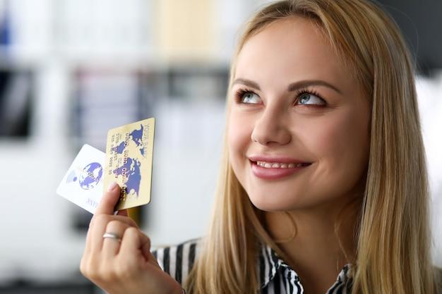Schöne blonde erwachsene kaukasische frau im bürogriff zwei kreditkarten