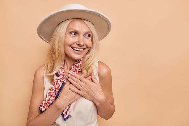 Schöne blonde europäische dame hält die hände ans herz gedrückt sieht mit bewunderung und freude aus, fühlt sich dankbar lächelt breit trägt fedora-kleid und kerchied um den hals gebunden isoliert auf beige wand