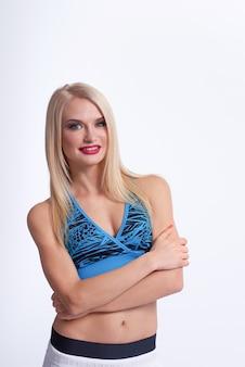 Schöne blonde fitnessfrau, die mit ihren verschränkten armen lächelt, die sicher posieren