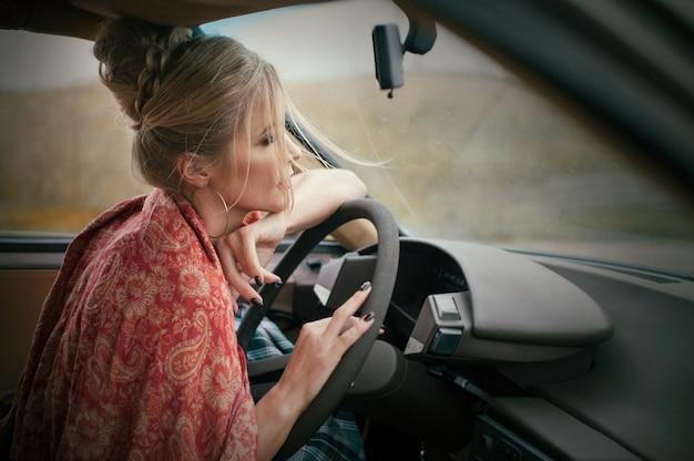 Schöne blonde frau am französischen stil, der ein retroauto am regnerischen tag fährt, entspannen herbststimmung