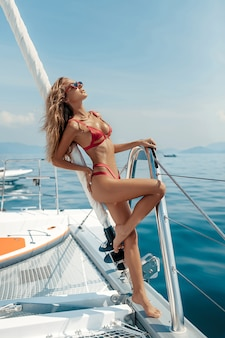 Schöne blonde frau auf der yacht, die reizvollen roten bikini und rote sonnenbrillen trägt