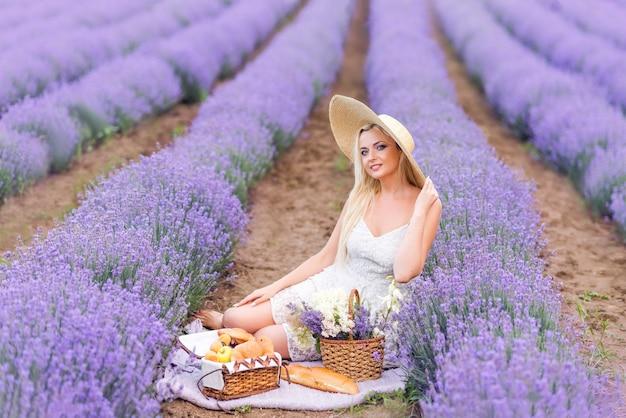 Schöne blonde frau auf einem picknick in einem lavendelfeld.