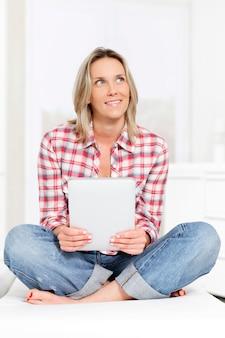 Schöne blonde frau auf sofa mit tablette