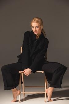 Schöne blonde frau auf stuhl
