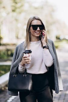 Schöne blonde frau, die am telefon spricht, das auf straße geht. stilvolle lächelnde geschäftsfrau mit kaffee in der dunklen freizeithose, im cremigen pullover und in der sonnenbrille. weiblicher geschäftsstil. hohe auflösung.
