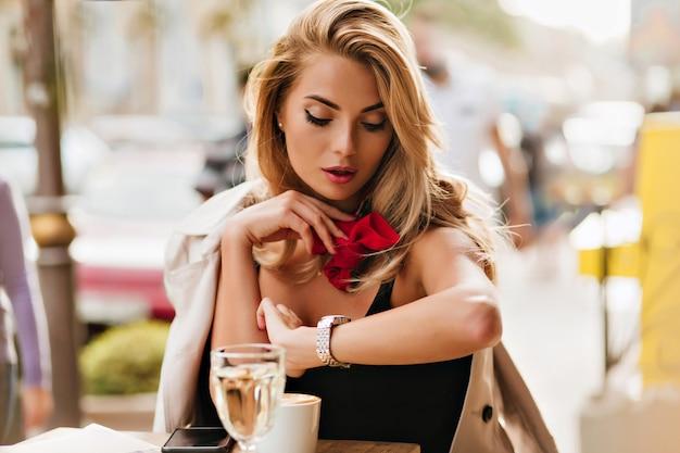 Schöne blonde frau, die armbanduhr beim kaffeetrinken im restaurant im freien betrachtet. porträt der ernsten dame mit rotem schal, der auf freund wartet, der spät ist.