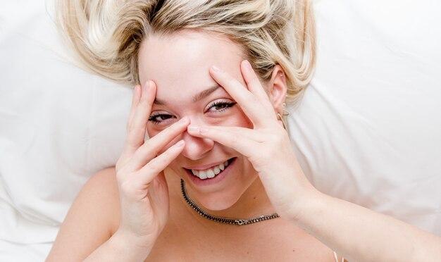 Schöne blonde frau, die auf dem bett liegt, das gesicht mit händen bedeckt