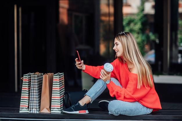 Schöne blonde frau, die auf der straße sitzt und von einkaufstüten umgeben ist und am telefon schaut.