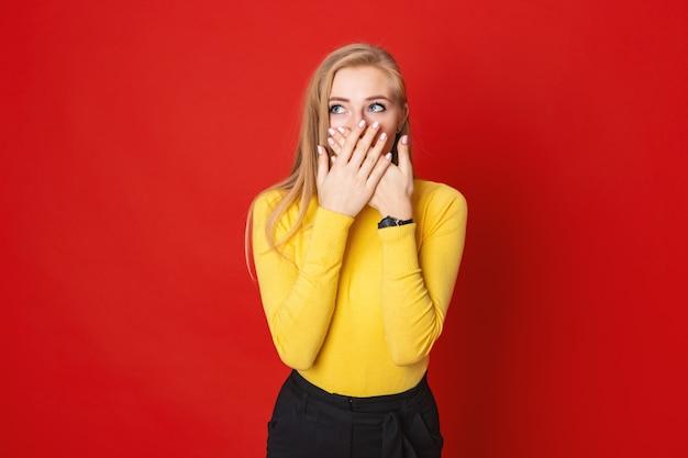 Schöne blonde frau, die auf einem roten hintergrund steht