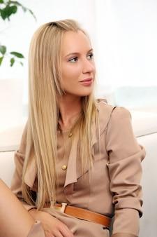 Schöne blonde frau, die auf einem trainer sitzt