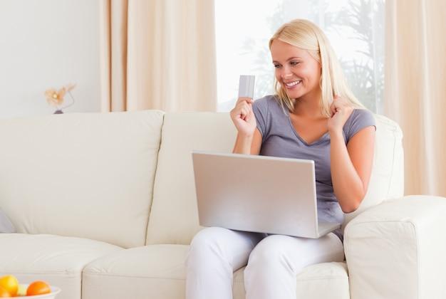 Schöne blonde frau, die beim online kaufen zujubelt