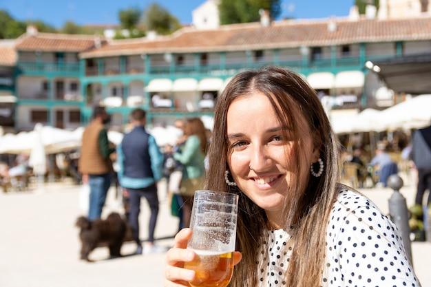 Schöne blonde frau, die bier in einem typischen dorfplatz trinkt