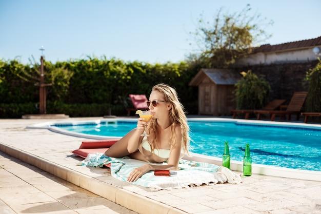 Schöne blonde frau, die cocktail trinkt, sonnenbaden, nahe schwimmbad liegend