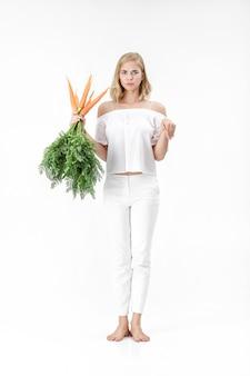 Schöne blonde frau, die das kaninchen zeigt und eine frische karotte mit grünen blättern auf einem weißen hintergrund hält. gesundheit und ernährung