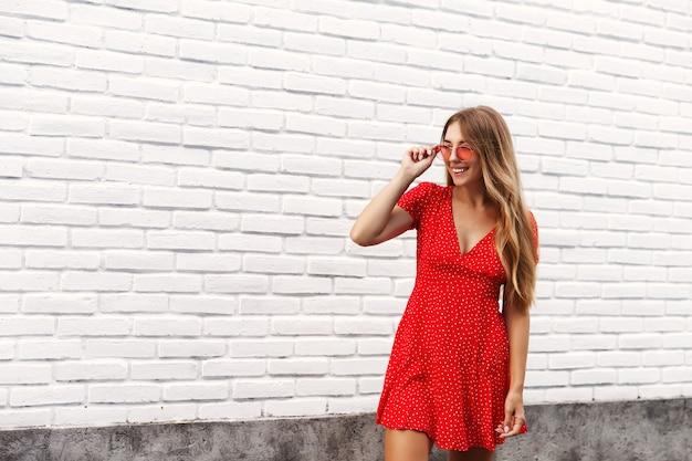 Schöne blonde frau, die die straße mit glücklichem gesicht geht, sonnenbrille und rotes kleid tragend