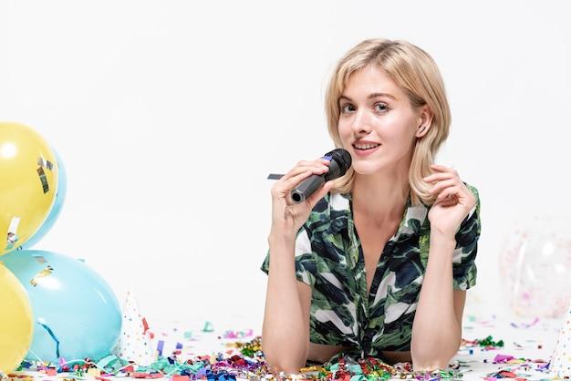 Schöne blonde frau, die ein mikrofon anhält