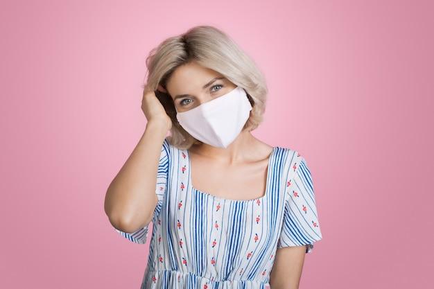 Schöne blonde frau, die eine anti-grippe-maske trägt, die in einem sommerkleid auf rosa wand lächelt, die ihr haar berührt