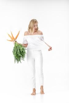 Schöne blonde frau, die eine frische karotte mit grünen blättern auf einem weißen hintergrund hält. mädchen isst karotten und wird dünn