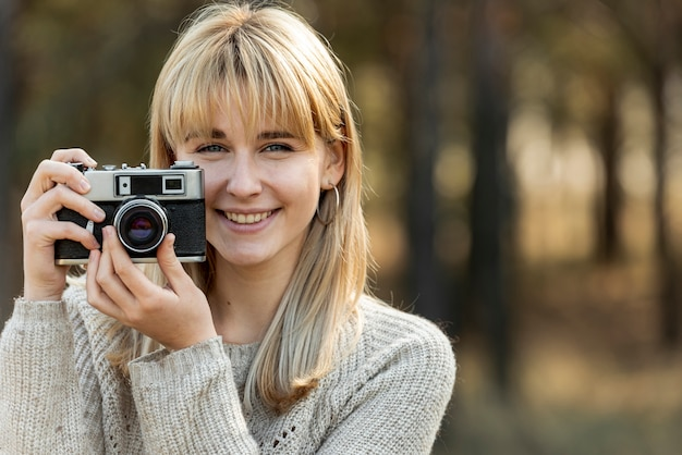 Schöne blonde frau, die eine weinlesekamera verwendet