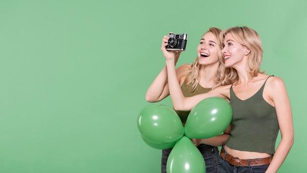 Schöne blonde frau, die fotos machend schaut