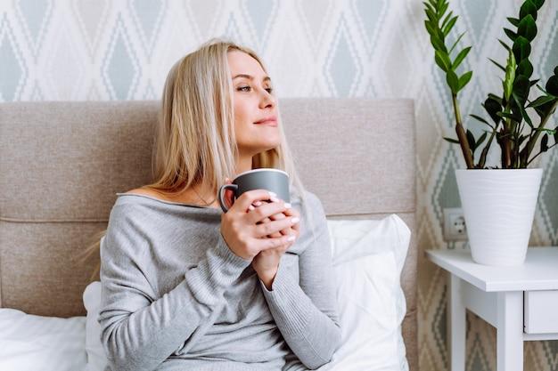Schöne blonde frau, die graue hauskleidung trägt, sitzt auf bett mit tasse kaffee im hellen schlafzimmer und schaut zum fenster.