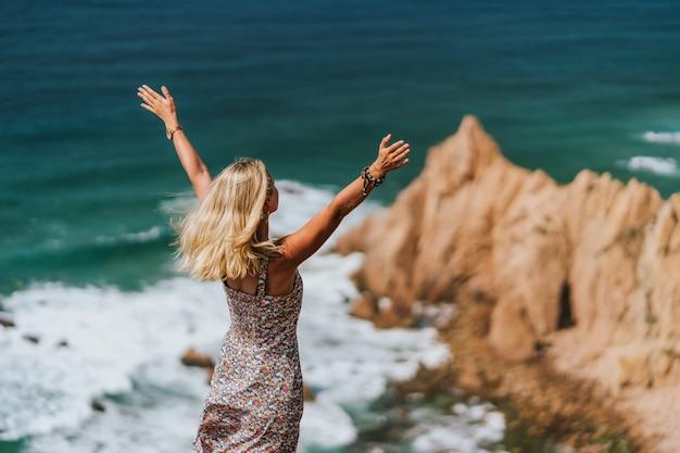 Schöne blonde frau, die hände hebt, die praia da ursa beach genießen. surreale landschaft von sintra