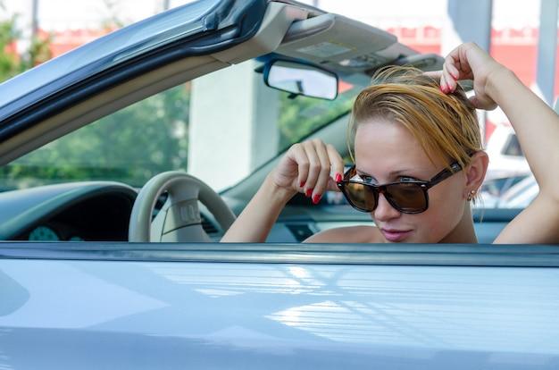 Schöne blonde frau, die ihr cabrioauto fährt