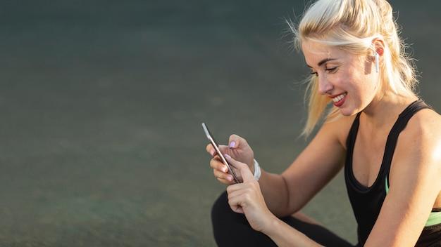 Schöne blonde frau, die ihr telefon überprüft