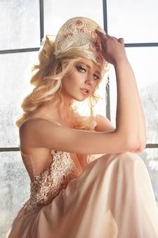 Schöne blonde frau, die im sonnenlicht fenster sitzt
