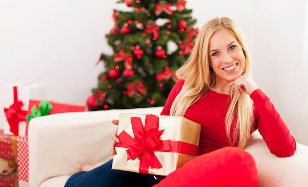 Schöne blonde frau, die im wohnzimmer während der weihnachtszeit sitzt