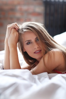 Schöne blonde frau, die in der roten unterwäsche auf bett aufwirft