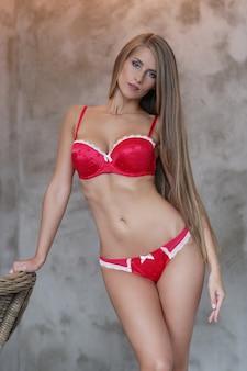Schöne blonde frau, die in der roten unterwäsche aufwirft