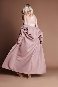 Schöne blonde frau, die in einem rosafarbenen mantel auf einer beige aufwirft