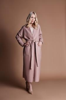Schöne blonde frau, die in einem rosafarbenen mantel aufwirft