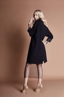 Schöne blonde frau, die in einem schwarzen mantel aufwirft