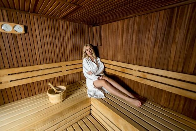 Schöne blonde frau, die in einer sauna entspannt