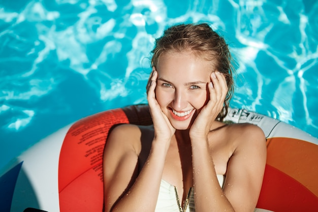 Schöne blonde frau, die lächelt, sich ausruht, sich entspannt, im pool schwimmt