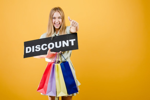 Schöne blonde frau, die mit dem rabattzeichen und bunten einkaufenbeuteln getrennt über gelb lächelt und schreit