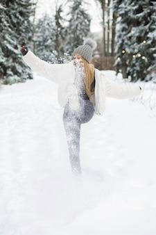 Schöne blonde frau, die mit schnee im wald spielt