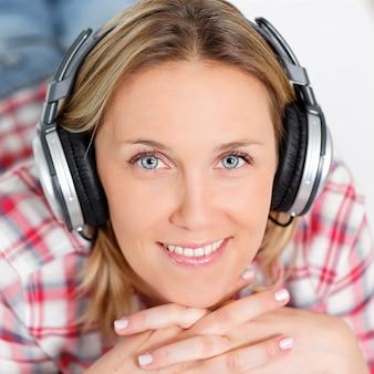 Schöne blonde frau, die musik mit kopfhörern hört