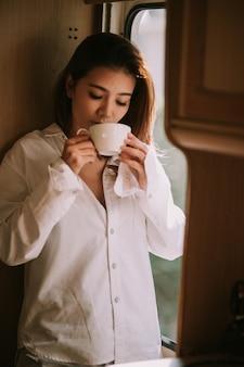 Schöne blonde frau, die neben einem fenster steht, männerhemd trägt und kaffee trinkt