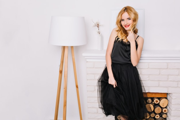 Schöne blonde frau, die neben moderner weißer stehlampe steht, schönes weißes interieur. fashinable dame lächelnd, elegantes schwarzes kleid tragend. sie hat ziemlich welliges haar.