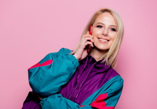 Schöne blonde frau, die per telefon auf rosa wand spricht