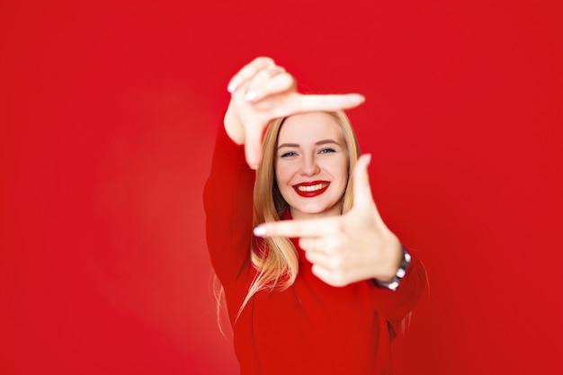 Schöne blonde frau, die quadratische abbildung von den fingern zeigt