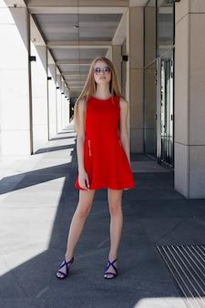 Schöne blonde frau, die rotes kleid und sonnenbrille trägt. elegantes und schönes frauenportrait