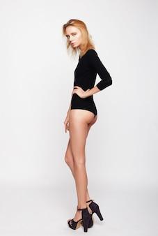 Schöne blonde frau, die schwarze modische dessous trägt, studio schoss über weißem hintergrund